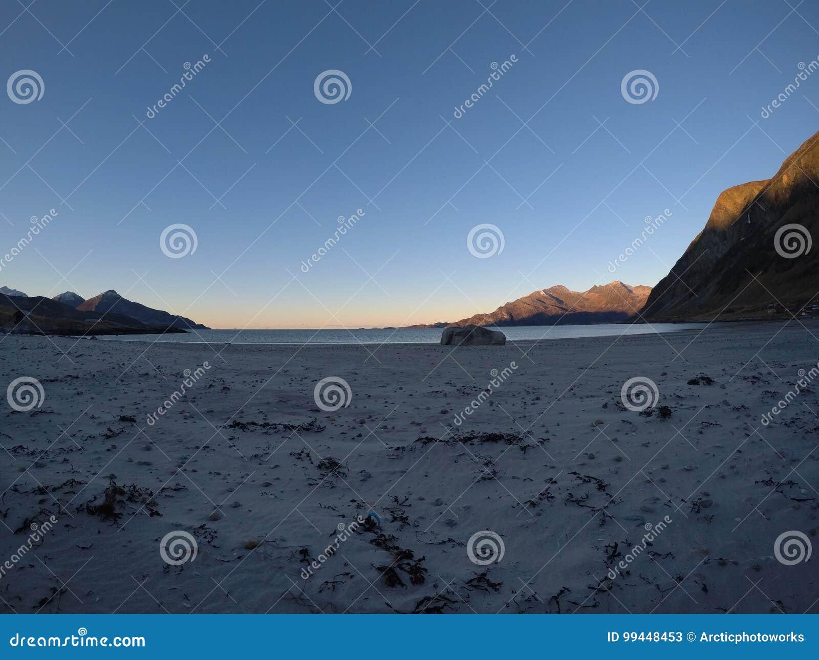 Piękne spokojne błękit fala uderza białą marznącą piaskowatą plażę w opóźnionej jesieni w arktycznym okręgu z głęboką górą i otwa