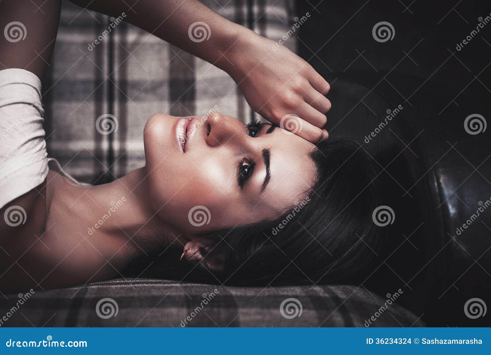 Pięknego brunetka splendoru seksowna kobieta pozuje na leżance