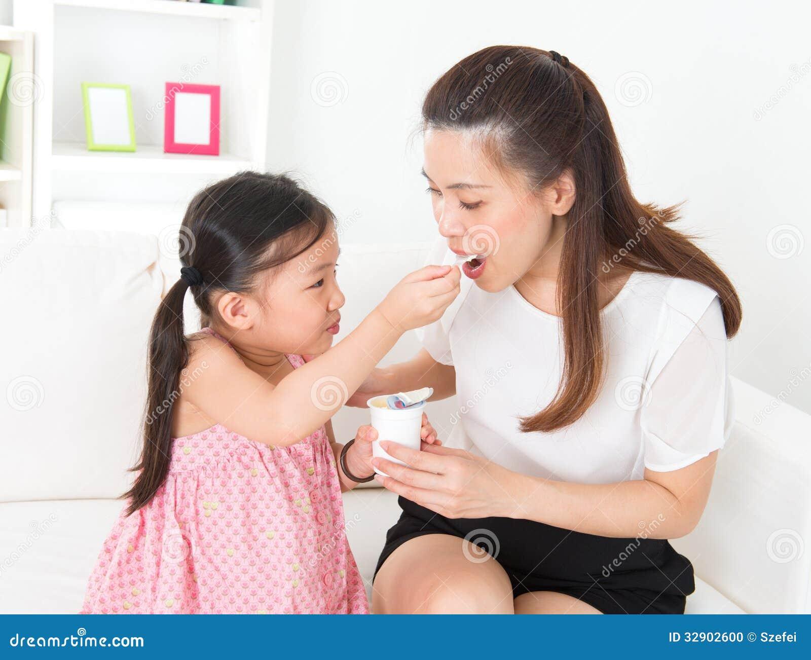 Pięknego dziecka karmienia matki jogurt