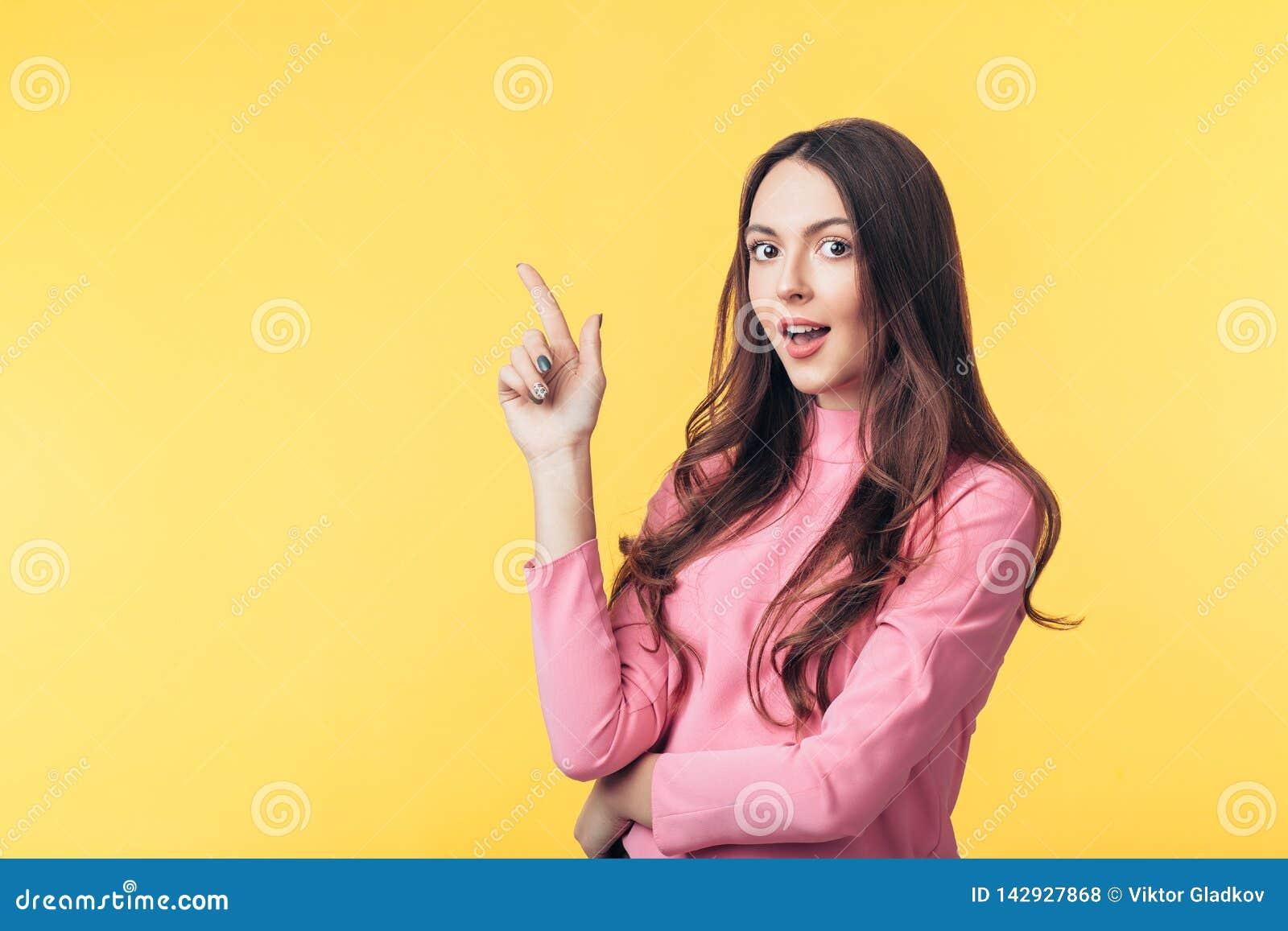 Pięknego zdziwionego kobieta seansu pusta kopia astronautyczna wskazujący ona palce odizolowywający na żółtym tle