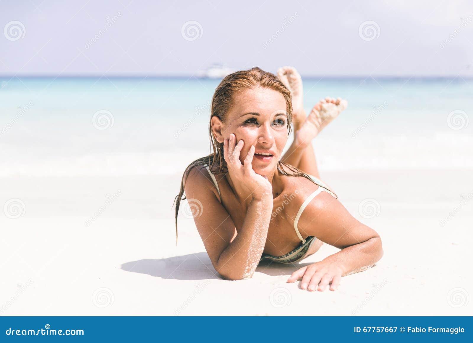 Pięknej kobiety łgarski puszek na tropikalnej plaży