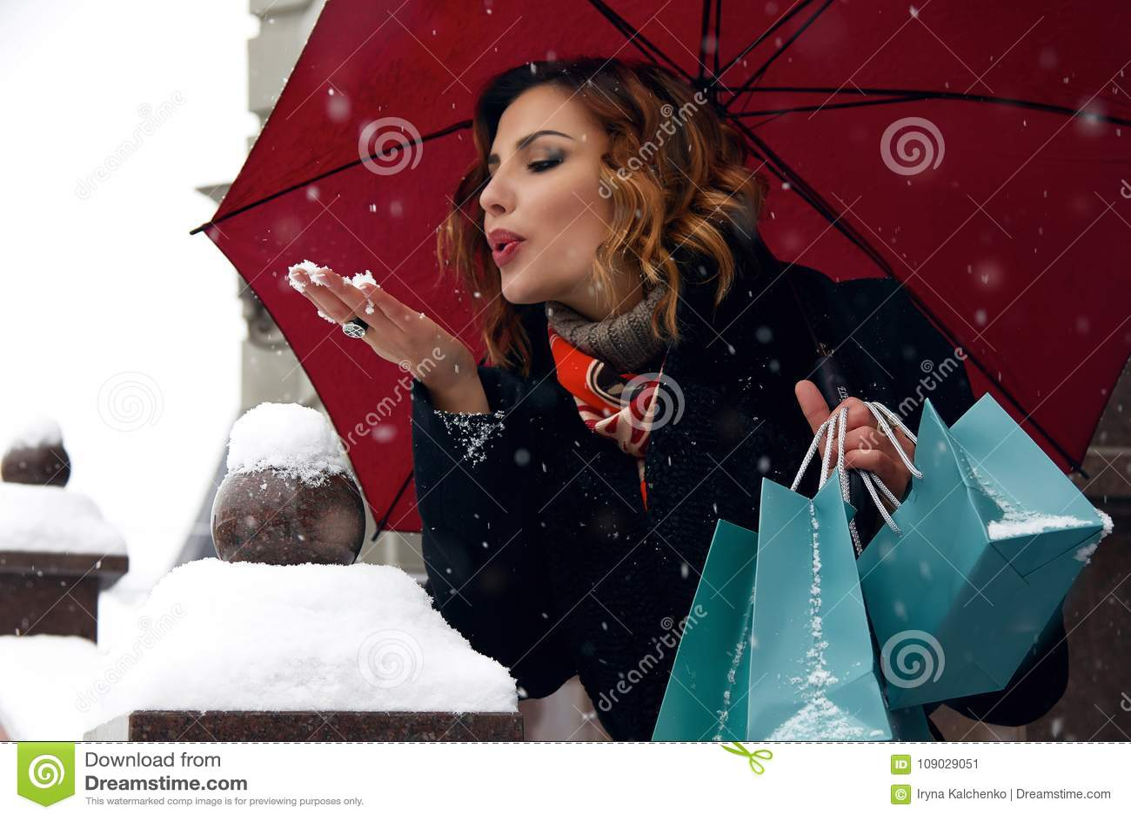 Pięknej kobiety śnieżny uliczny zakup przedstawia Bożenarodzeniowego nowego roku