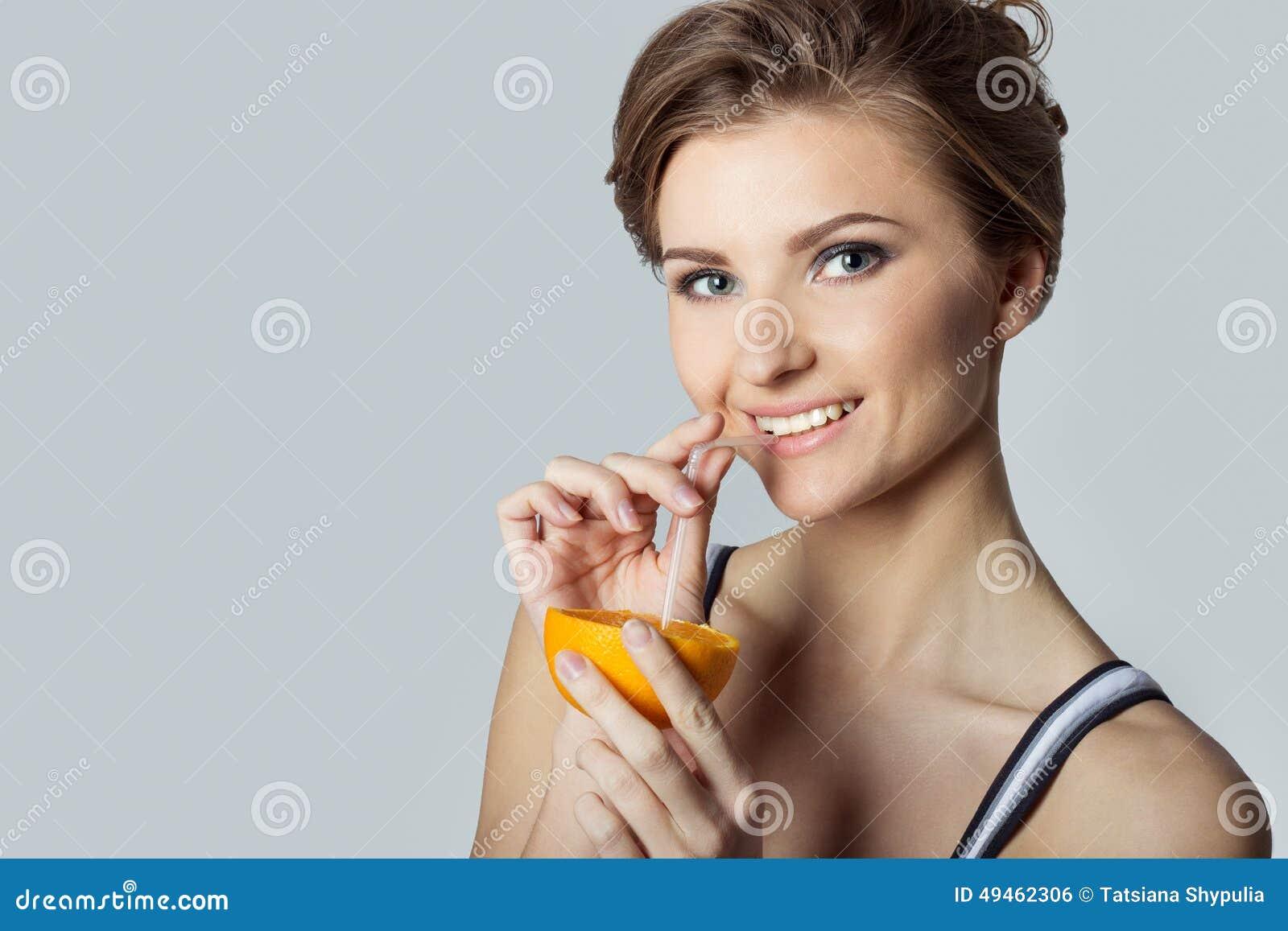 Pięknej młodej sportowej dziewczyny energiczny szczęśliwy pije sok pomarańczowy, zdrowy styl życia