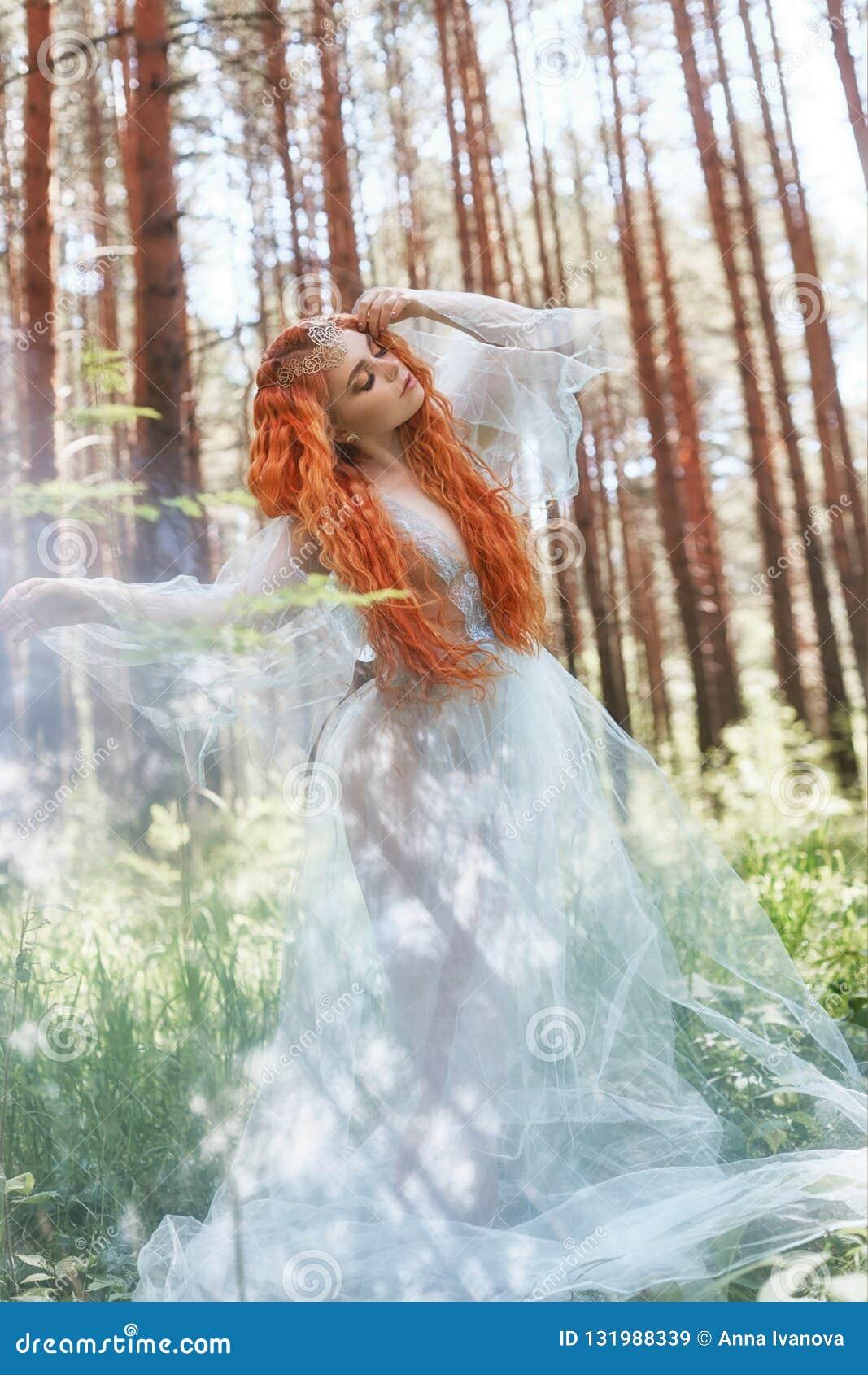 Pięknej rudzielec kobiety lasowa boginka wiruje w tanu w błękitnej przejrzystej światło sukni w drewnach Czerwone włosiane dziewc