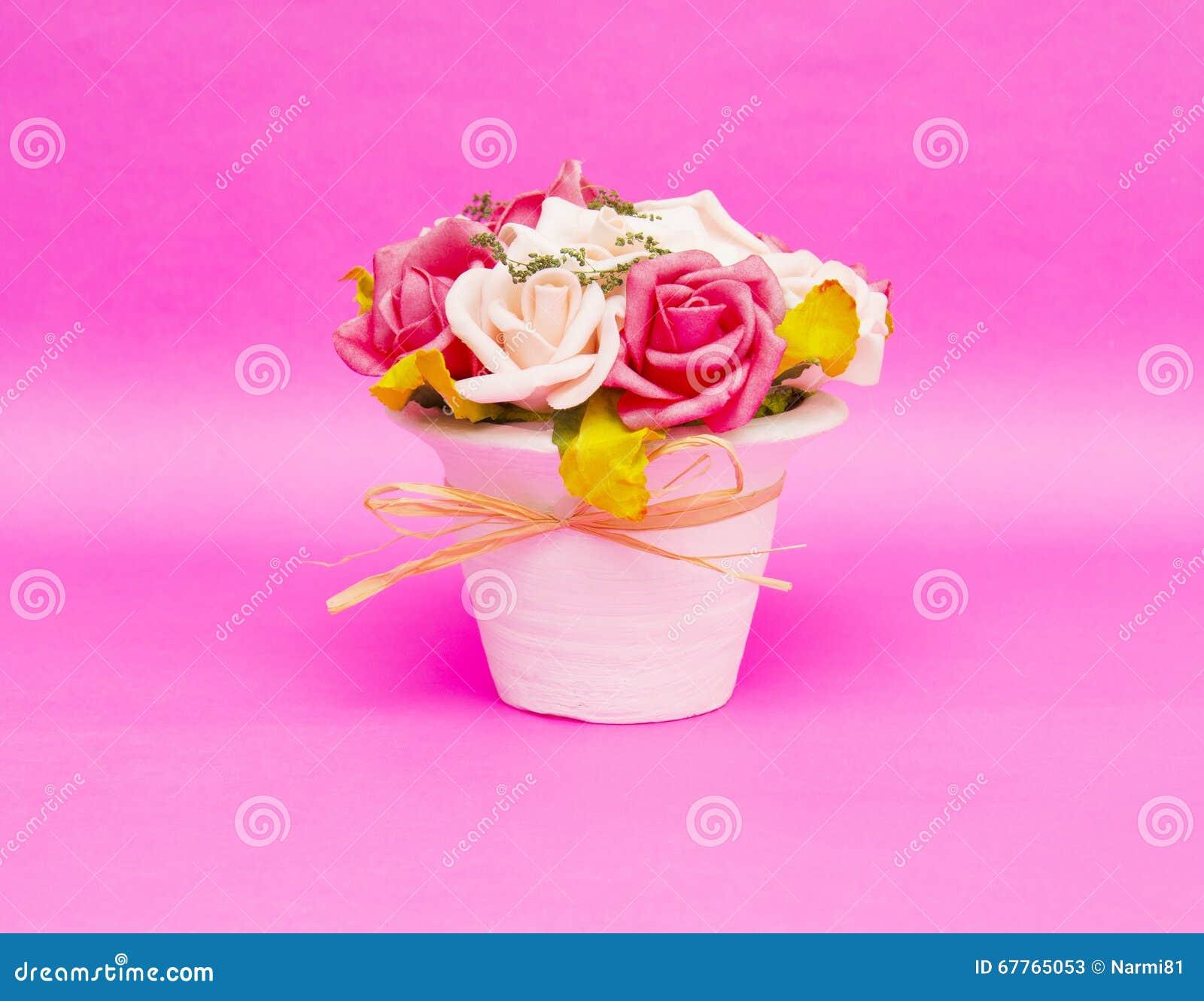Piękni kwiaty w wazie odizolowywającej na różowym tle