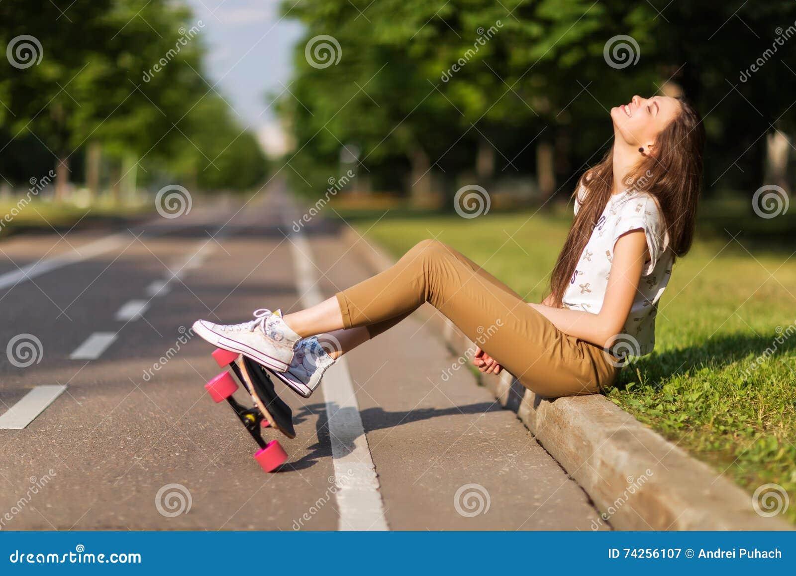 Piękni młoda dziewczyna modnisia sneakers koszulka i spodnia stawiają dalej sneakers i longboard szczęśliwych _ lifestyle