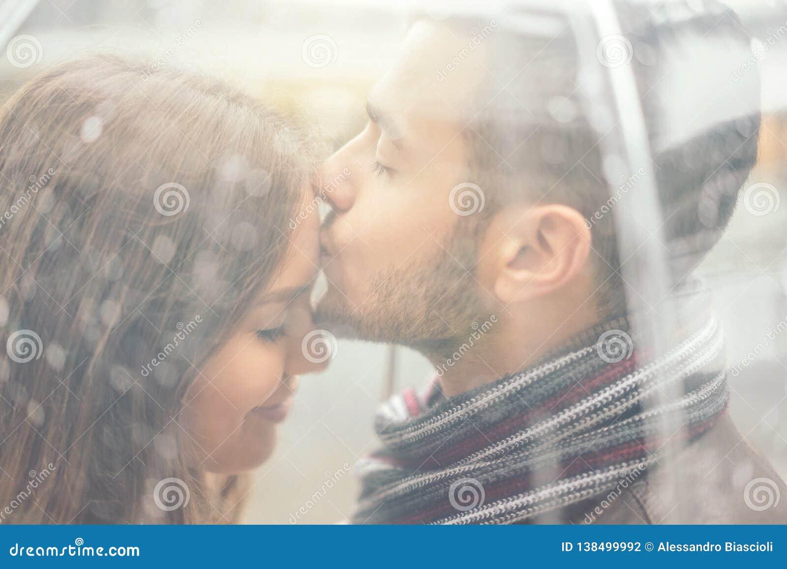 Piękni potomstwa dobierają się mieć romantycznego czułego moment pod deszczem - Przystojny mężczyzna całuje jego dziewczyny czoło