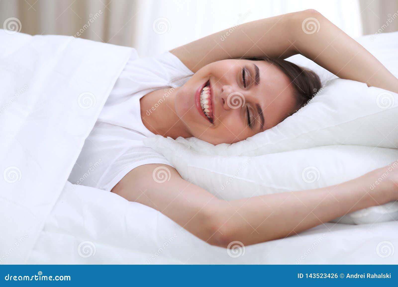 Piękni potomstwa i szczęśliwy kobiety dosypianie podczas gdy kłamający w łóżku swobodnie i blissfully ono uśmiecha się