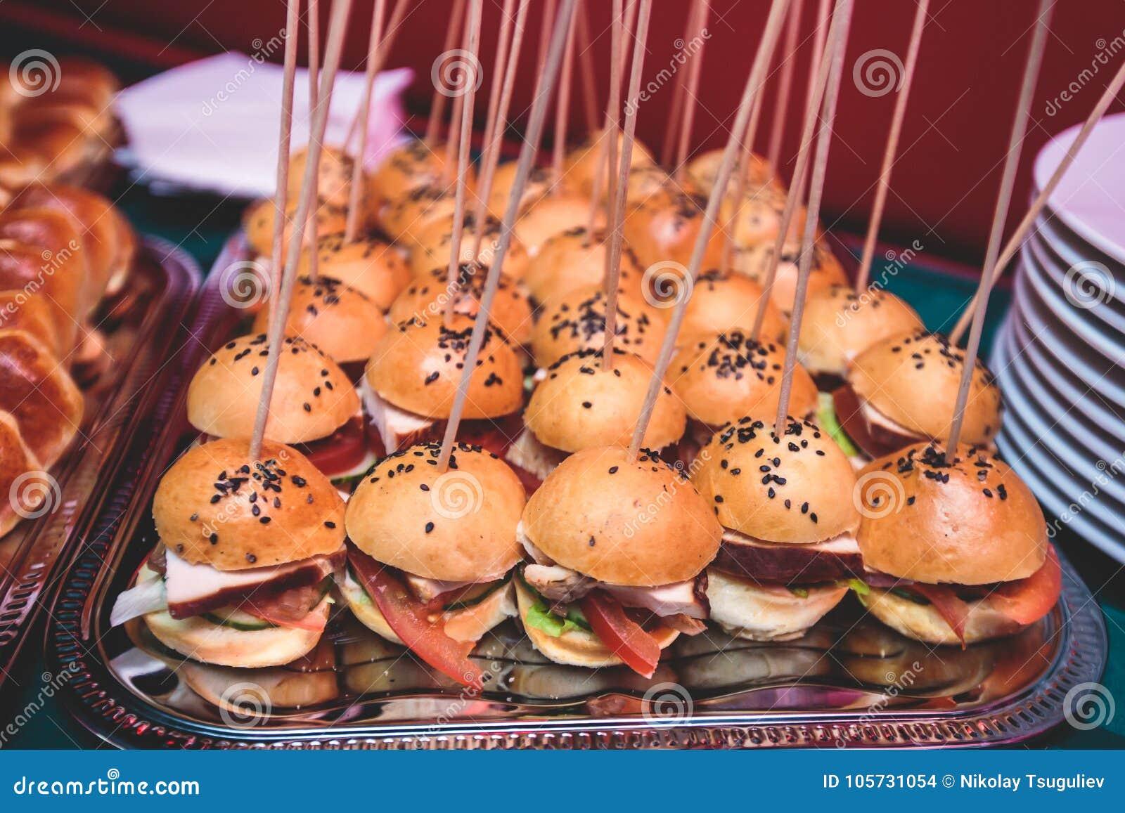 Pięknie dekorujący cateringu bankieta stół z różnymi hamburgerów hamburgerami ściska na talerzu na korporacyjnym bożego narodzeni