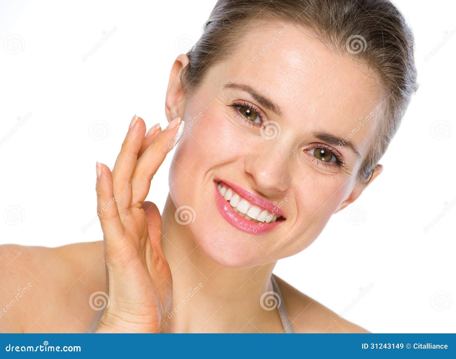 Piękno portret stosuje creme uśmiechnięta kobieta