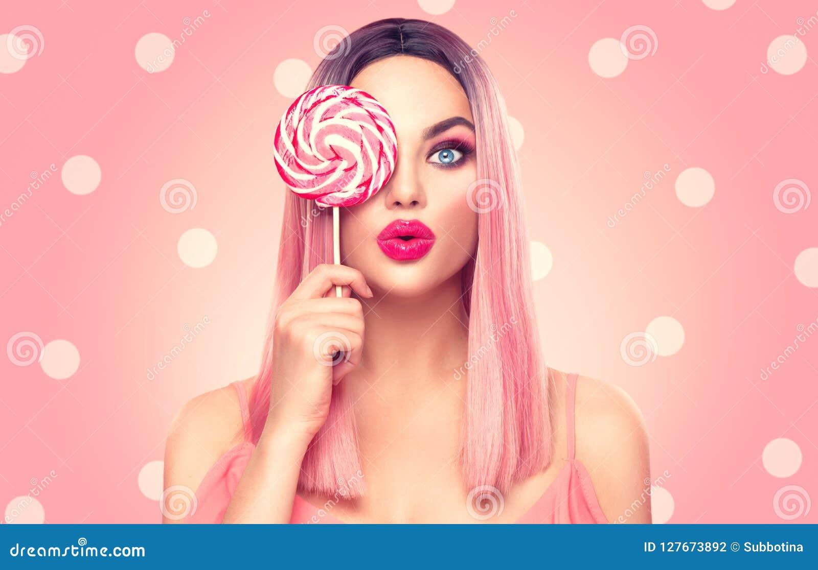 Piękno seksowna wzorcowa kobieta z modną różową fryzurą i pięknym makeup mienia lizaka cukierkiem
