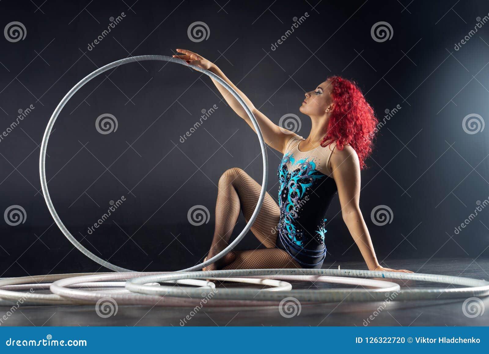 Piękny żeński czerwony włosiany cyrkowy artysta z obręcze