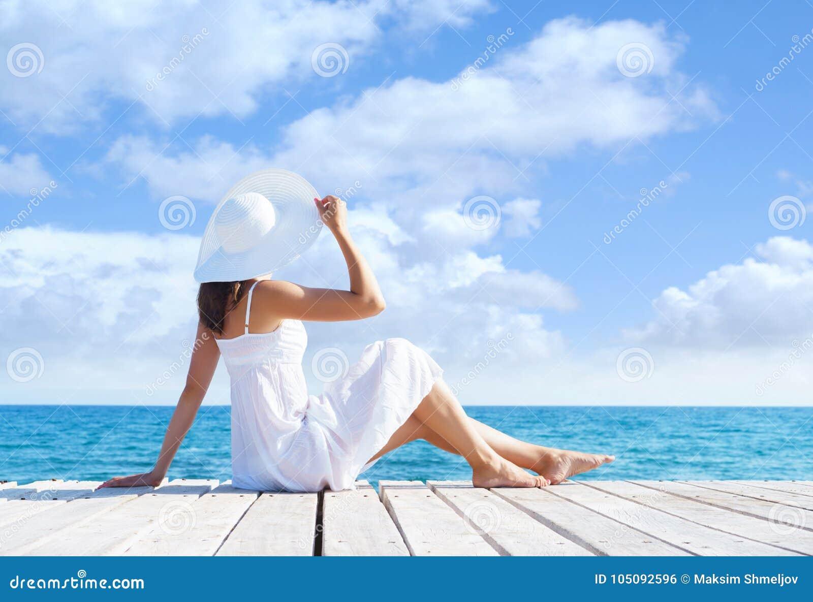 Piękny, atrakcyjny model pozuje w biel sukni na drewnianym molu, Morza i nieba tło Wakacje, podróżuje i