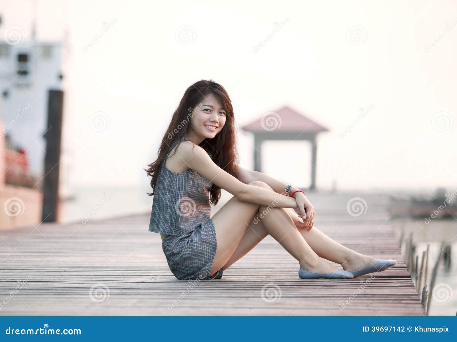 Piękny azjatykci kobiety obsiadanie na drewnianym molu z relaksującą emocją