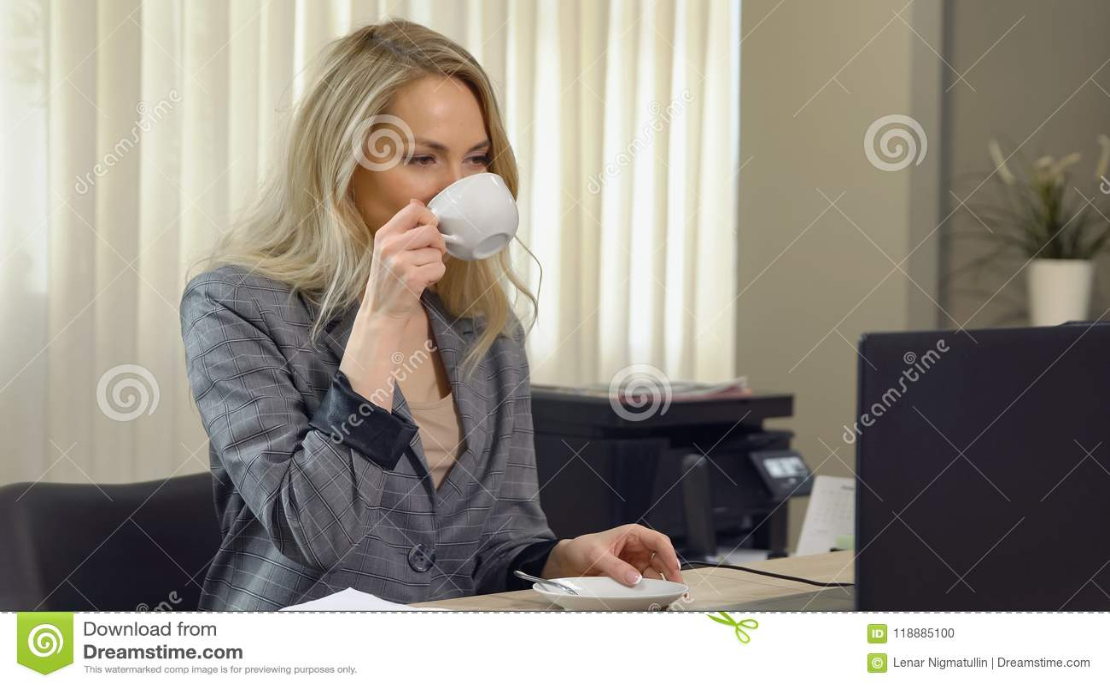 Piękny bizneswoman w kostiumu pracuje z filiżanki kawą przy miejscem pracy