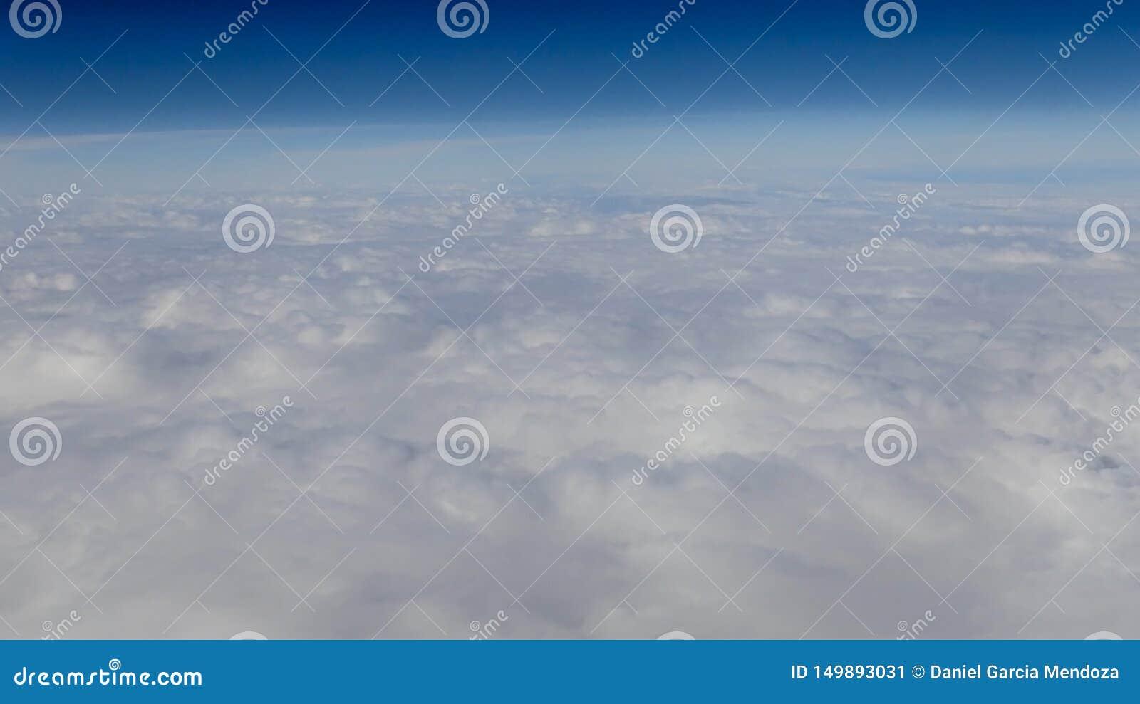 Piękny cloudscape z jasnym niebieskim niebem Widok od samolotowego okno
