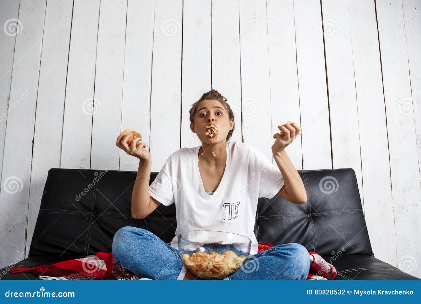 Piękny domowy dziewczyny łasowanie szczerbi się, dopatrywanie tv, siedzi przy kanapą