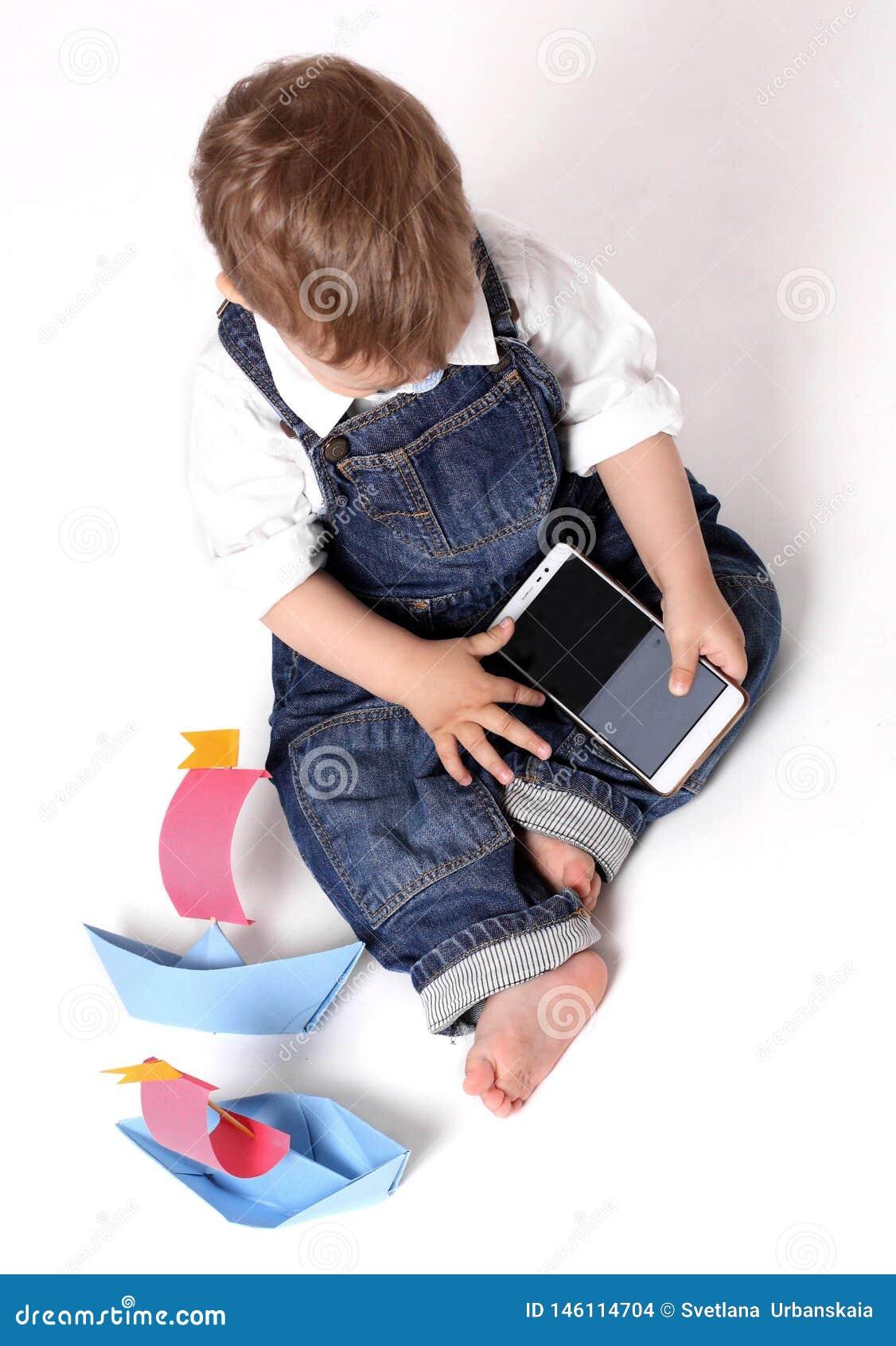 Pi?kny dziecko bawi? si? z m?drze telefonem odizolowywaj?cym na bia?ym tle