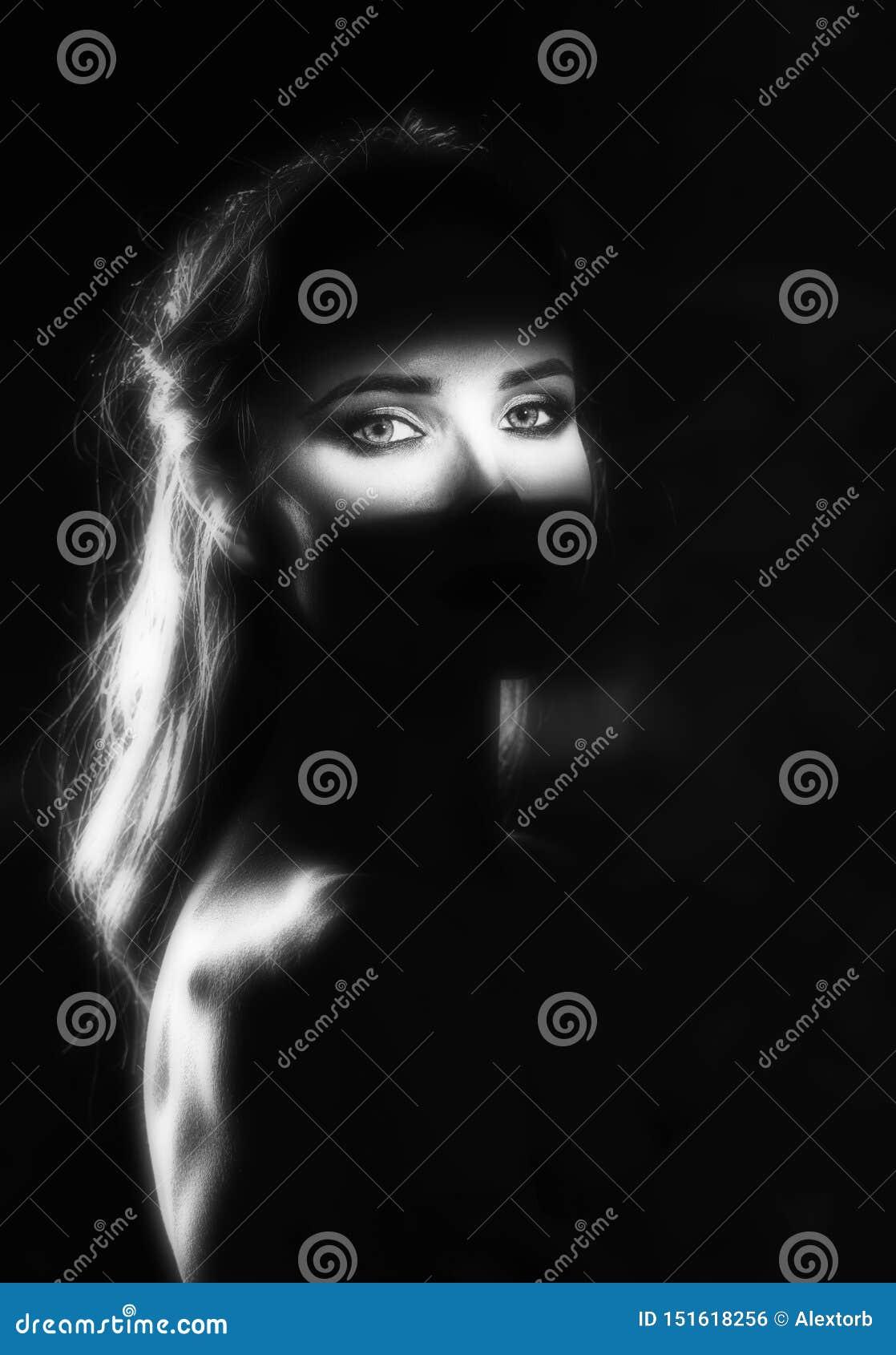 Piękny dziewczyna model z czerwonymi wargami uzupełnia i nadzy ramiona w cieniu z zaświecającą sylwetką i paskiem światło,