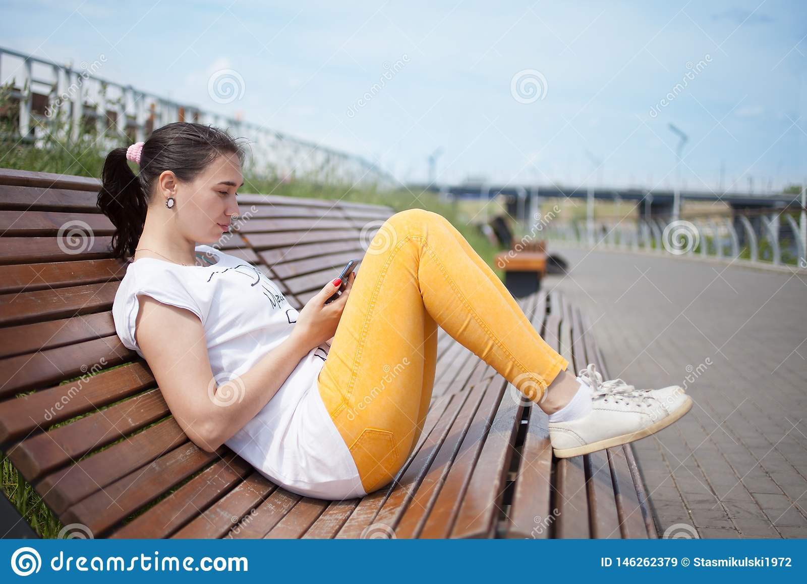 Piękny dziewczyny obsiadanie na ławce w parku z telefonem w rękach