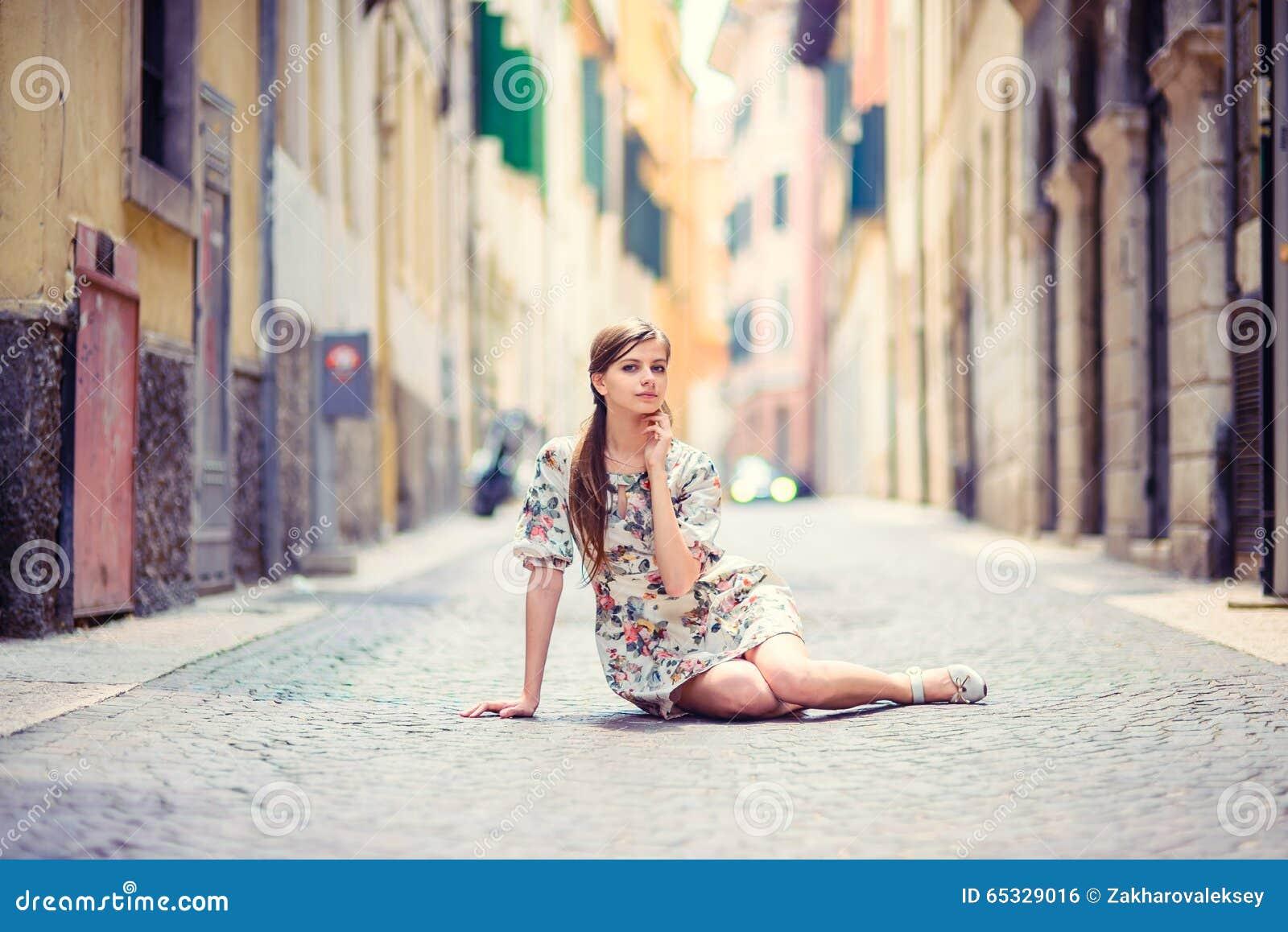 Piękny dziewczyny obsiadanie na ulicie