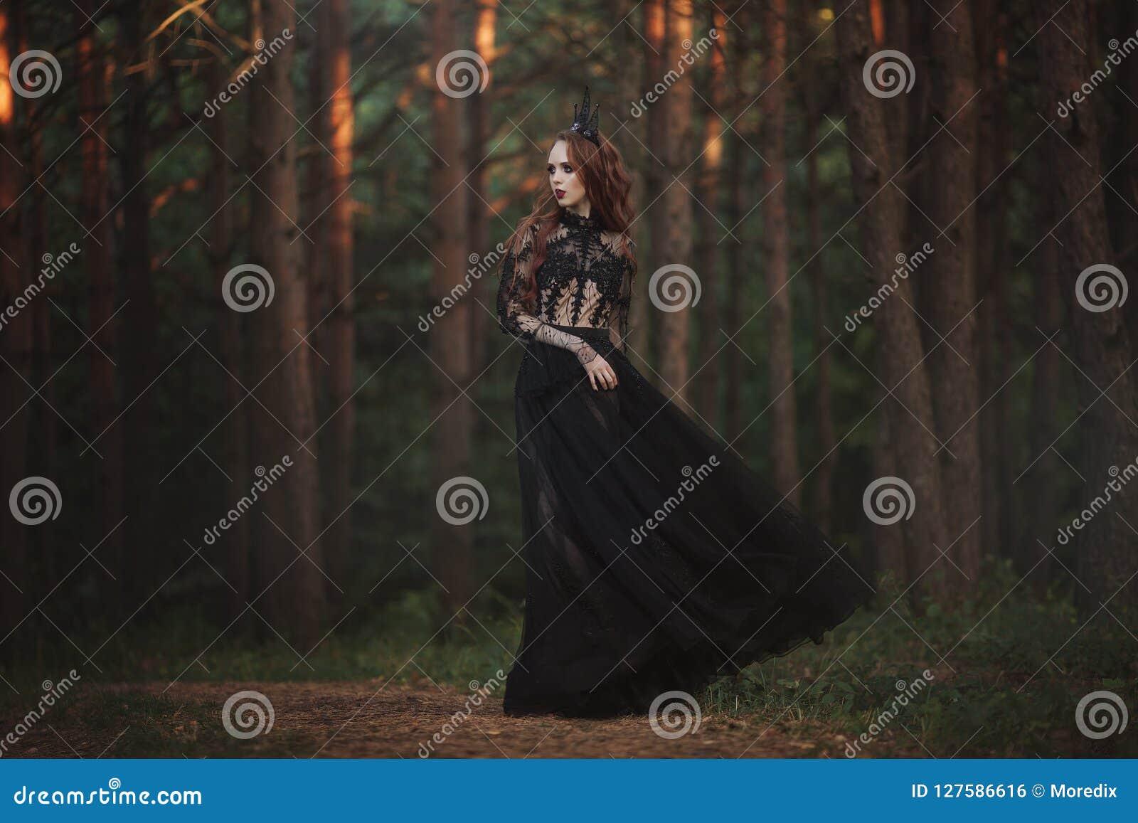 Piękny gothic princess z bladą skórą i bardzo tęsk czerwony włosy w czarnej koronie i czerni sukni w mglistym czarodziejskim lesi