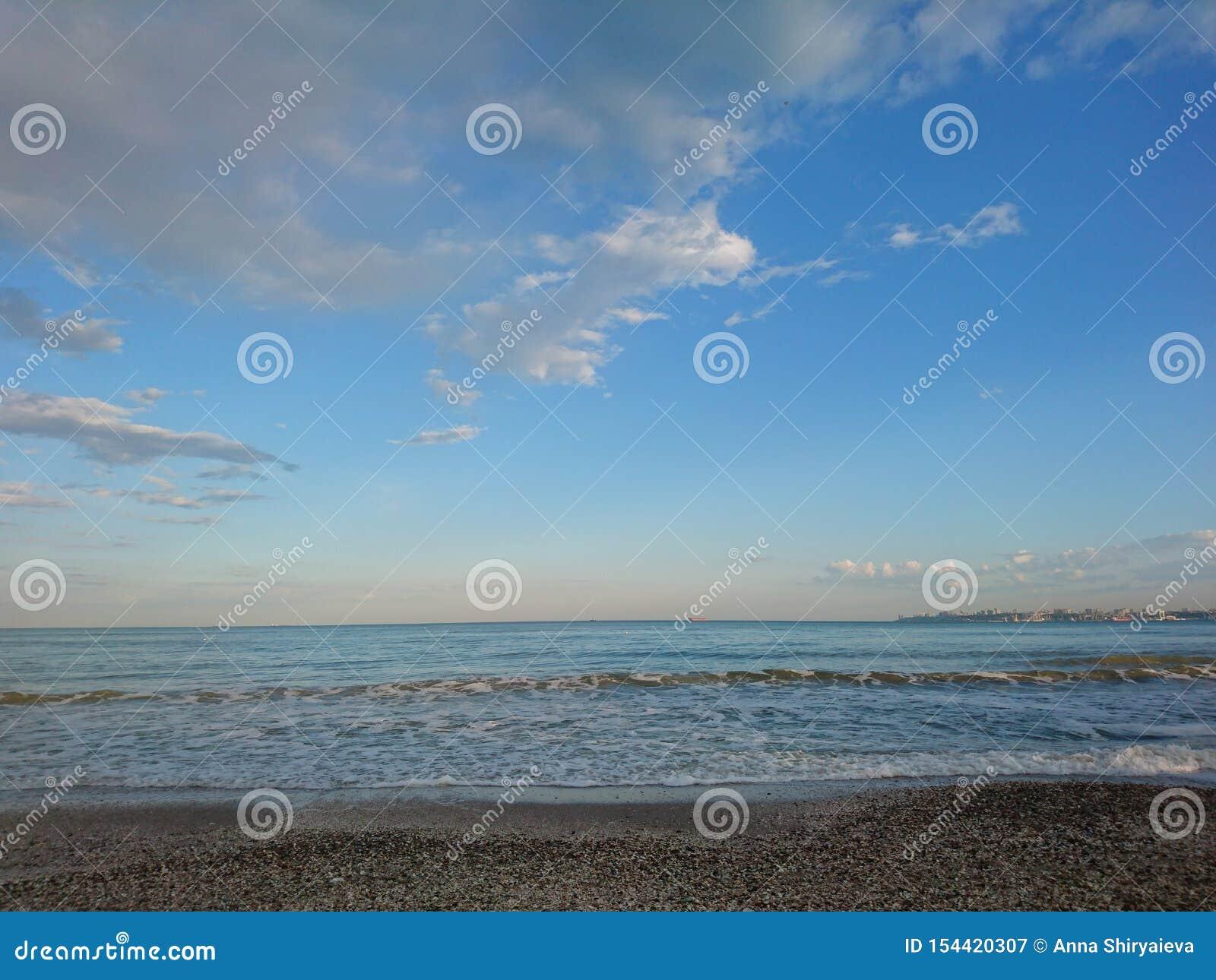 Piękny jaskrawy błękitny seascape: niebo, chmury, woda, fale, piasek, wiatr