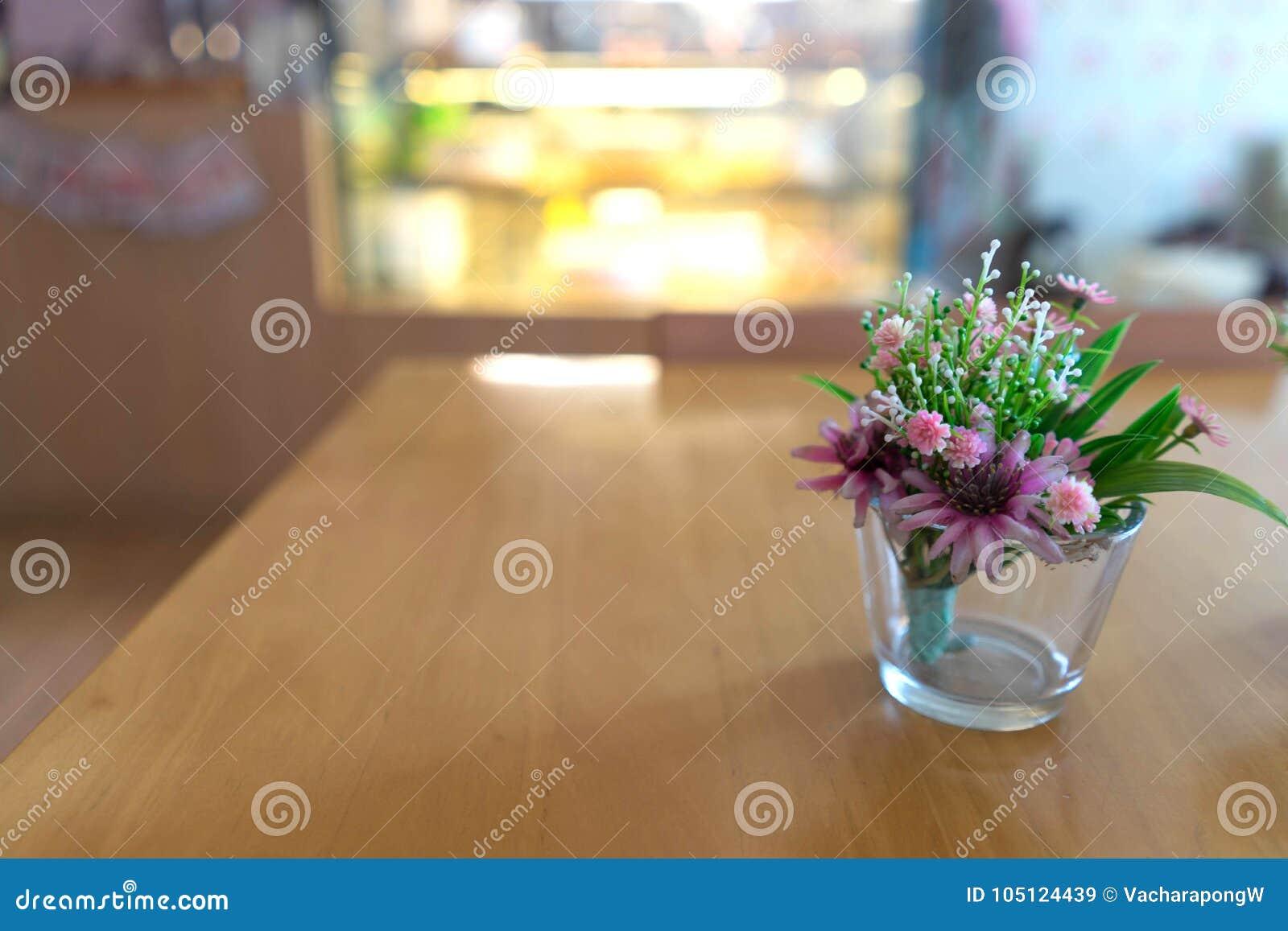 Piękny klingeryt kwitnie na szklanej wazie na drewnianym stole w piekarzie