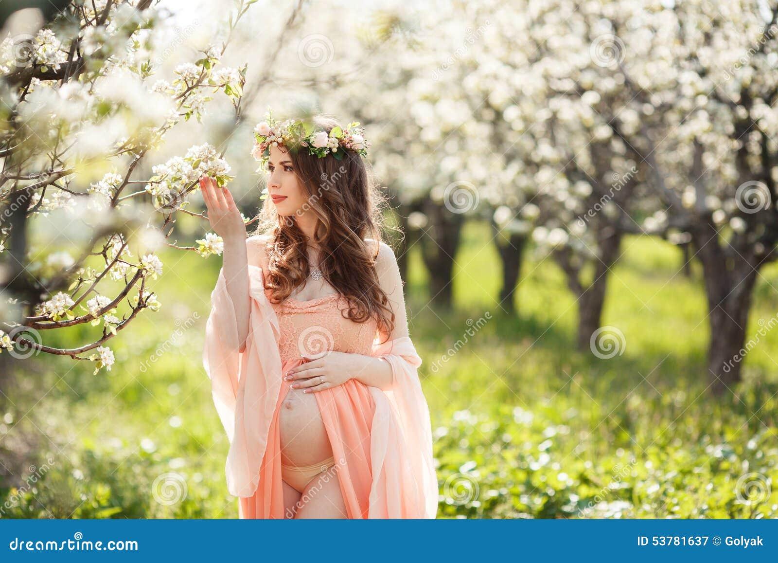 Piękny kobieta w ciąży w kwiaciastym wiosna ogródzie