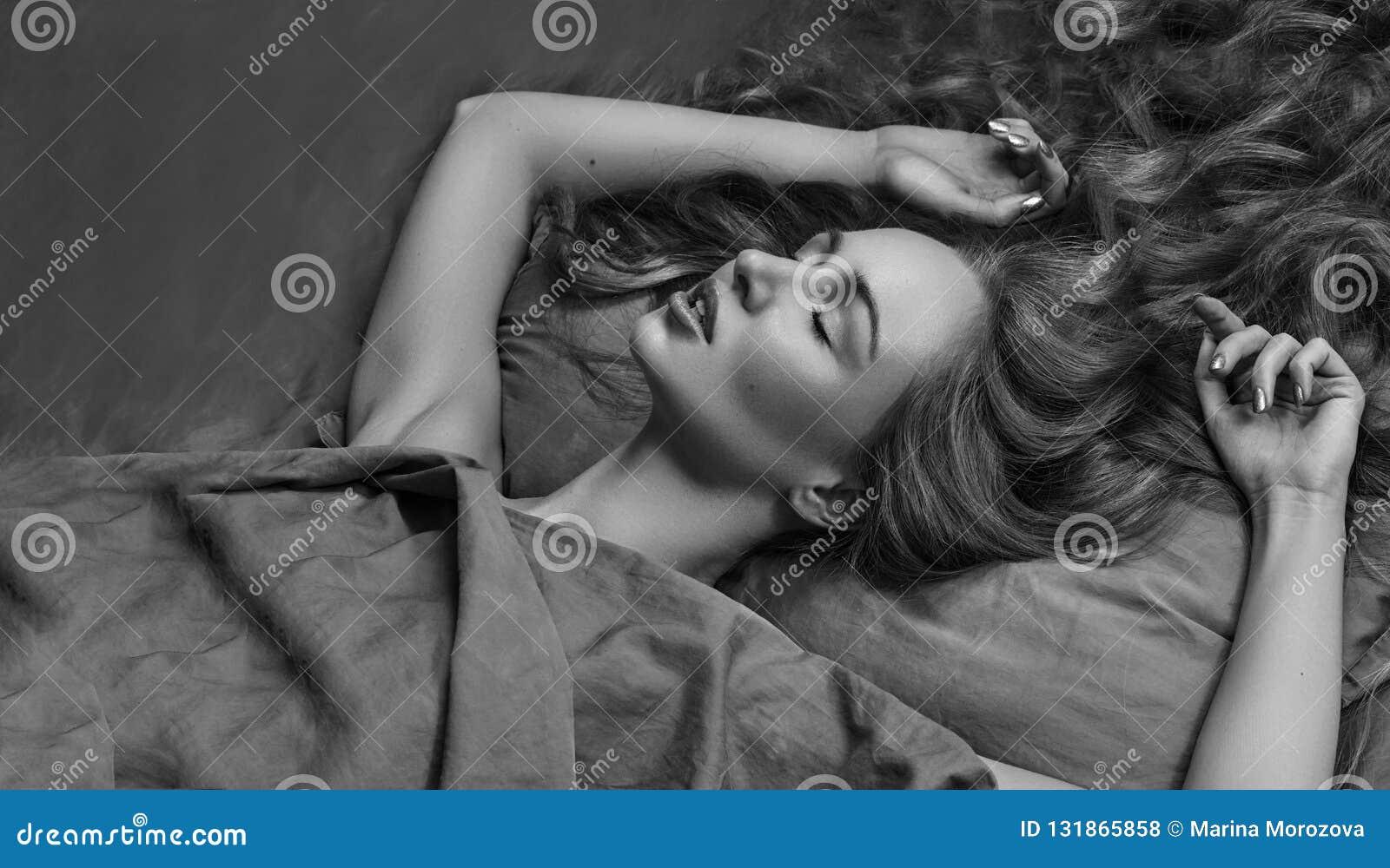 Piękny kobiety dosypianie podczas gdy kłamający w łóżku z wygodą słodki sen model z kędzierzawym włosy relaksuje na prześcieradła