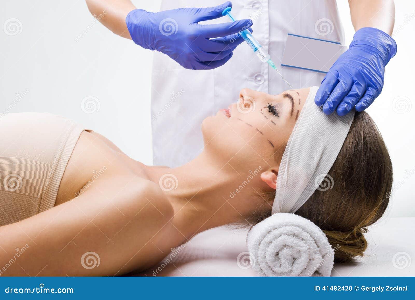 Piękny kobiety lying on the beach w klinice, chirurg plastyczny w rękach igła