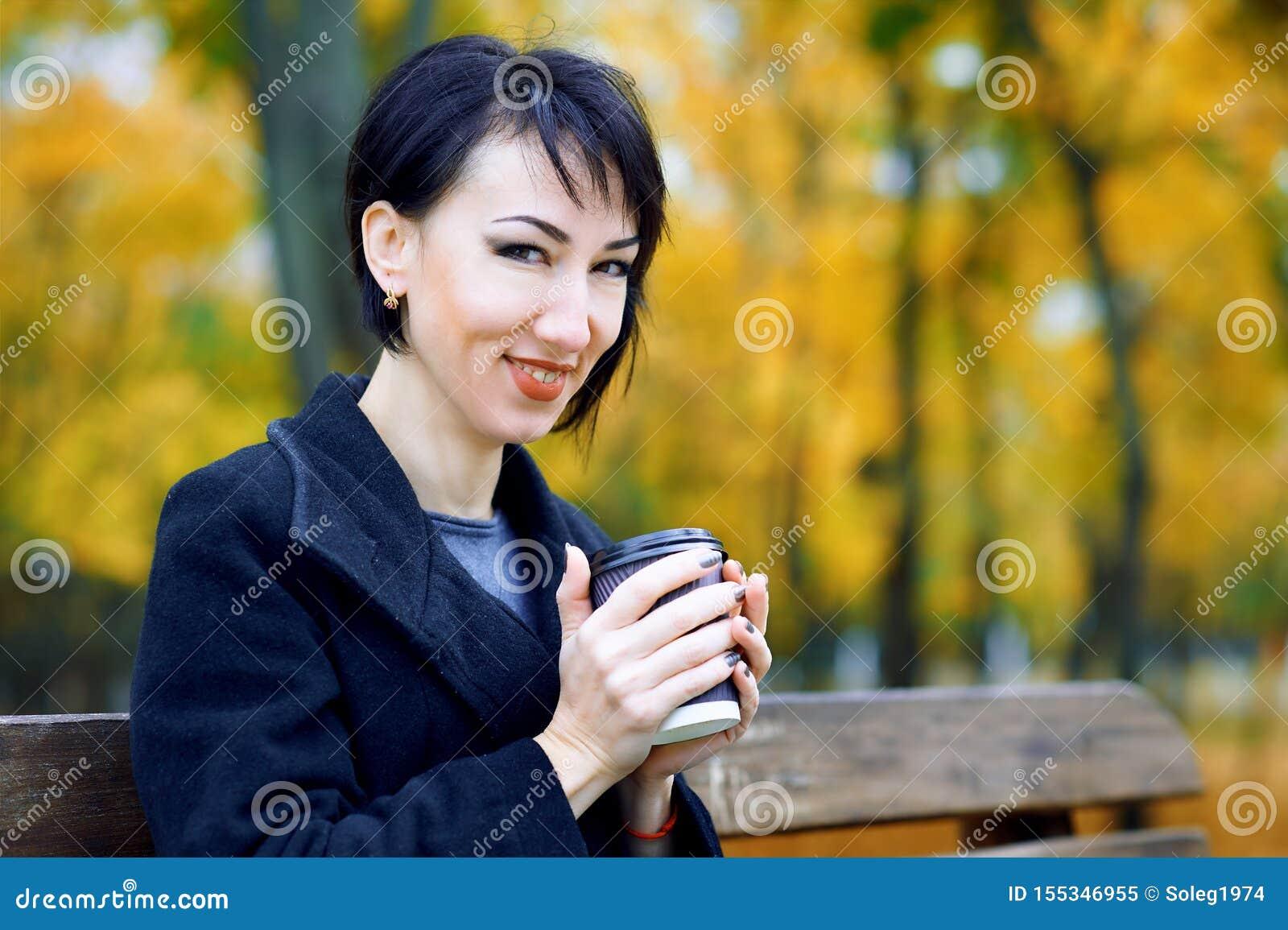 Piękny kobiety obsiadanie z kawą w jesieni miasta parku, sezon jesienny, kolor żółty opuszcza