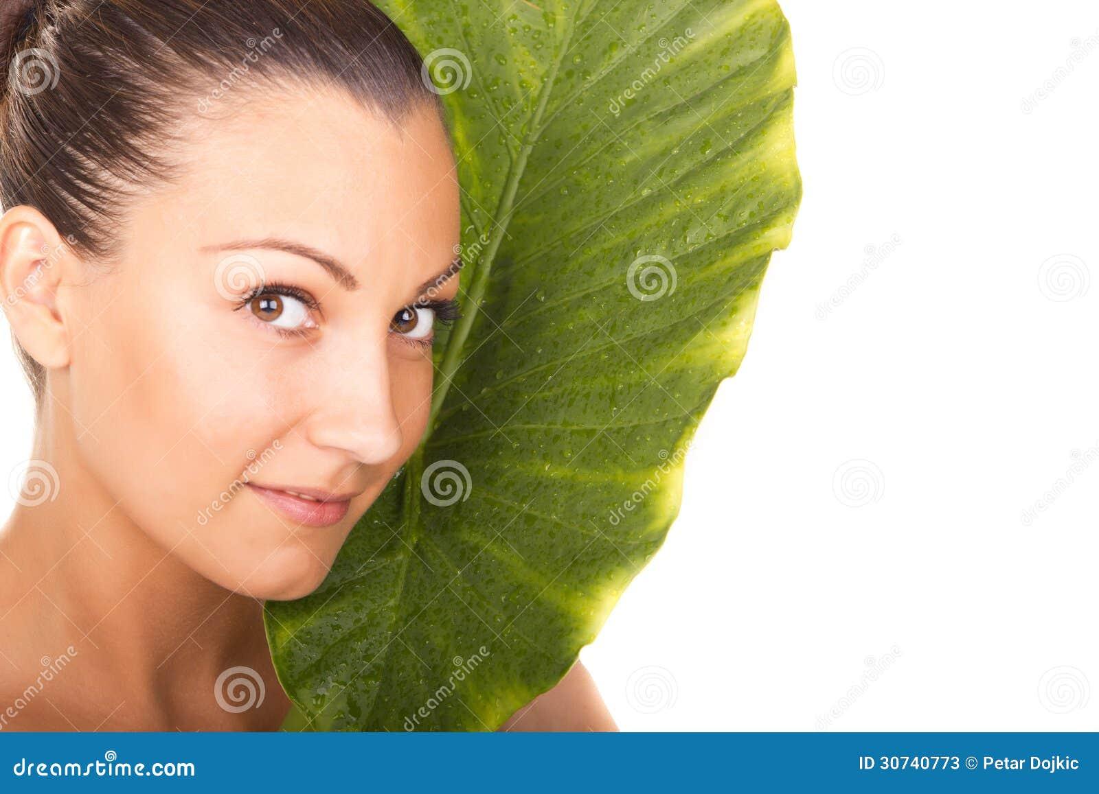 Piękny kobiety zbliżenia twarzy portret z zielonym liściem