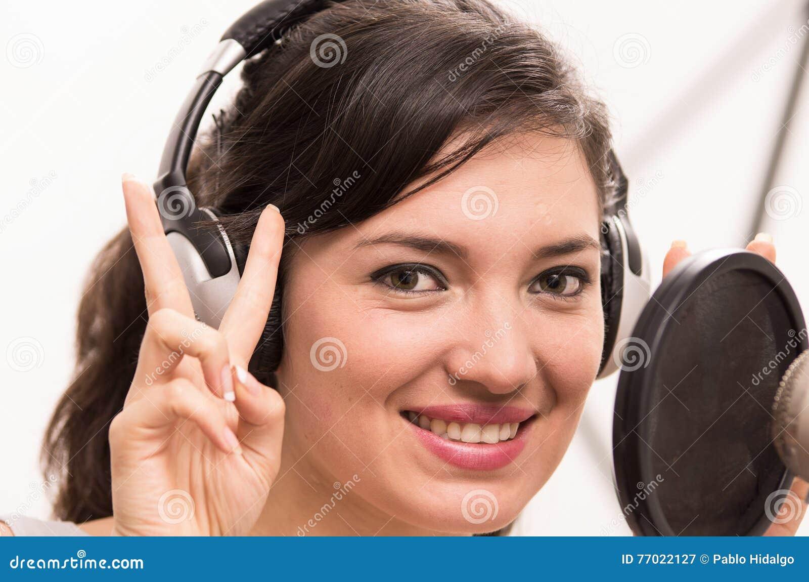 Piękny młoda dziewczyna śpiew w muzycznym studiu