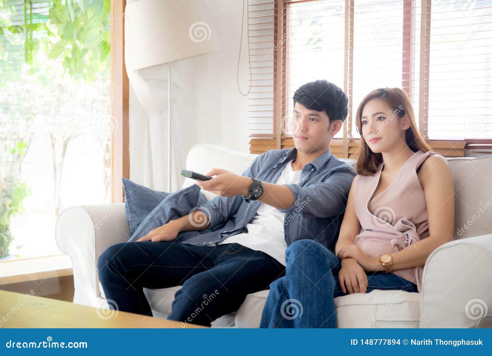 Piękny młody azjatykci pary mienia pilot, dopatrywanie tv i wideo leje się na kanapie z relaksujemy i szczęśliwy