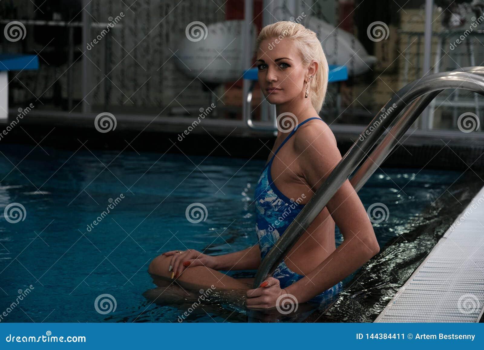 Piękny młody blondynki obsiadanie na krokach basen w wodzie obracającej i patrzeje kamerę