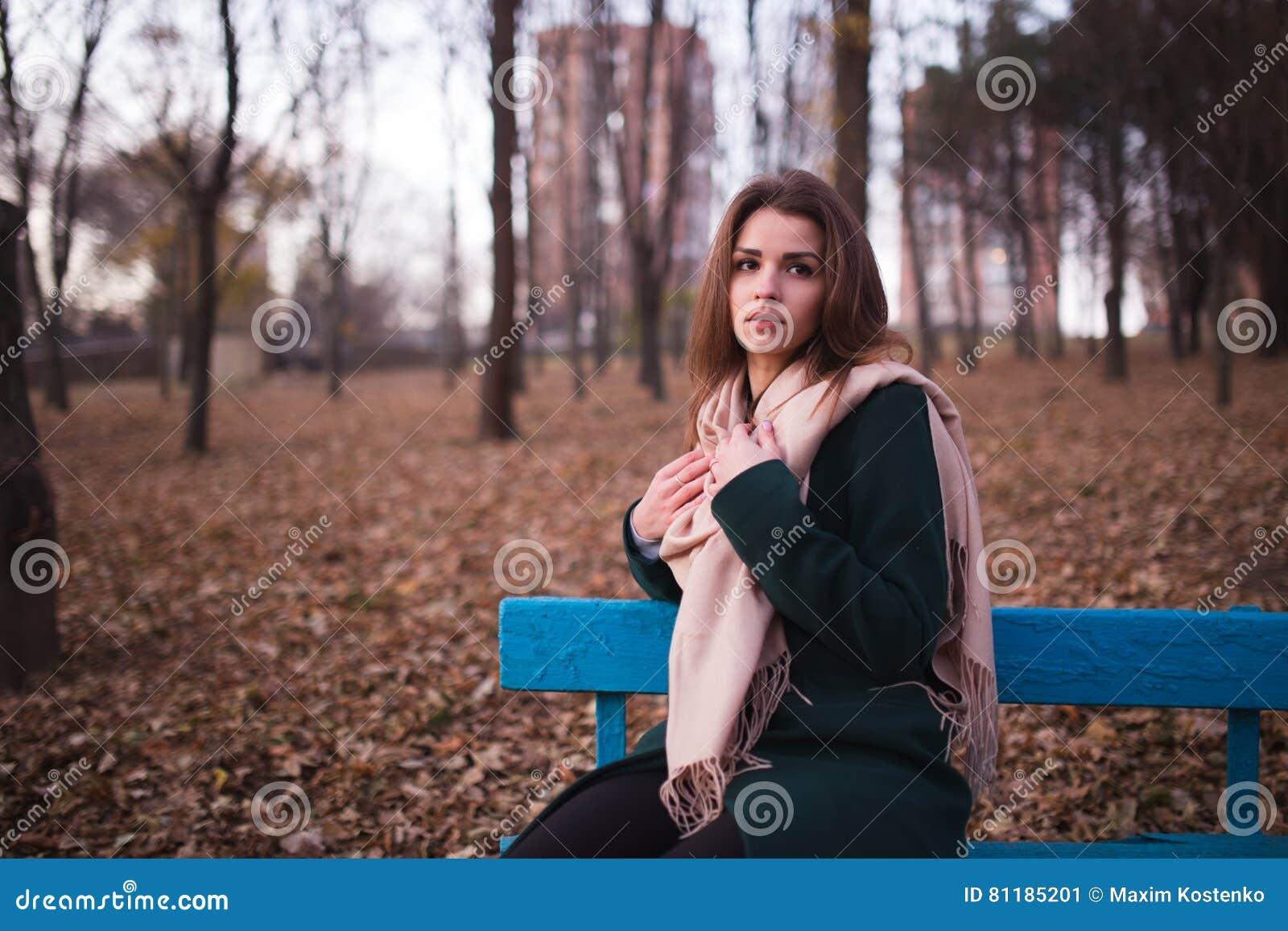 Piękny młody brunetki kobiety obsiadanie na ławce w jesień parku