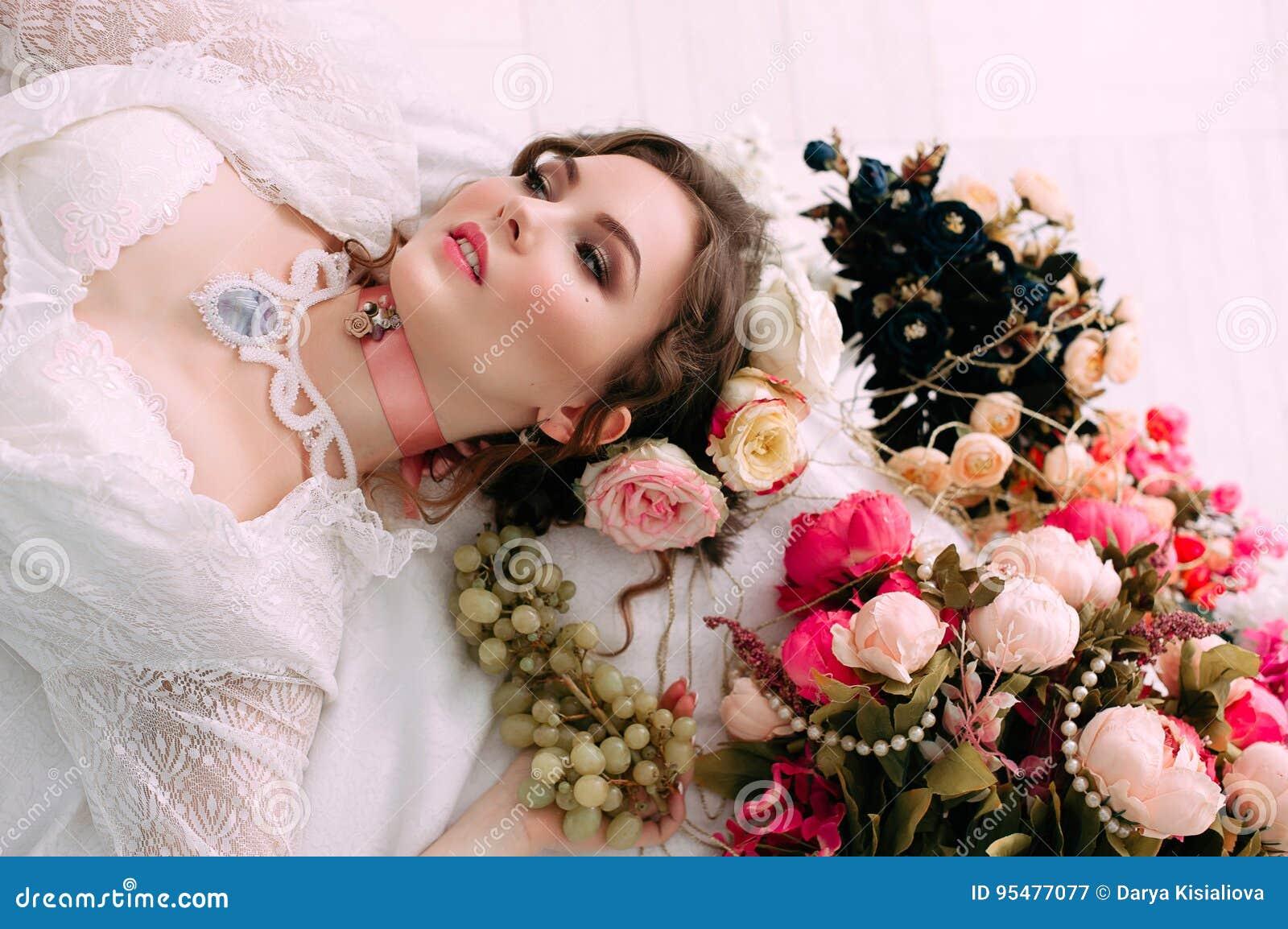 Piękny młody seksowny kobiety obsiadanie na białych łóżka i łasowania winogronach, jest ubranym biel koronki suknię, pokój dekoro