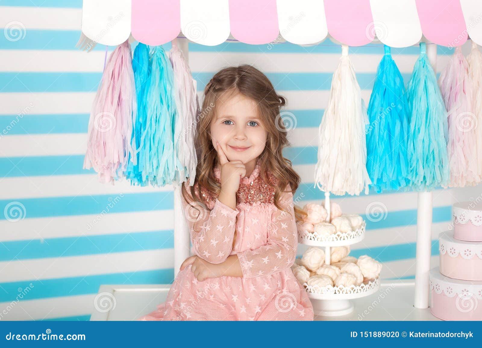 Piękny małej dziewczynki obsiadanie na stole z cukierkami Cukierku urodziny bar Portret dziecko twarzy zbliżenie Mała śliczna dzi