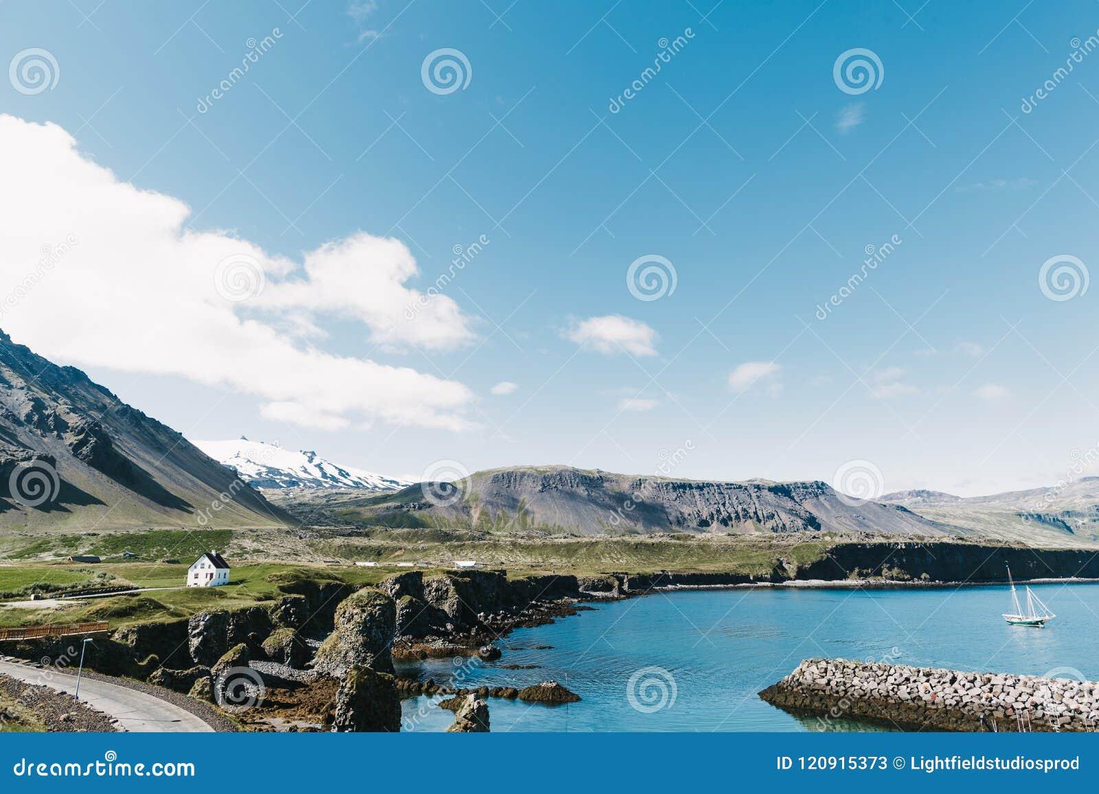 Piękny nadmorski z spławowym jachtem na wodzie, drodze, skalistych górach i domach na brzeg w gatklettur, arnarstapi, Iceland