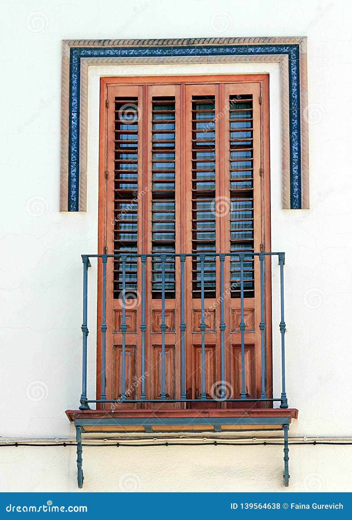Piękny okno z żaluzjami i mały balkon w Dos Hermanos