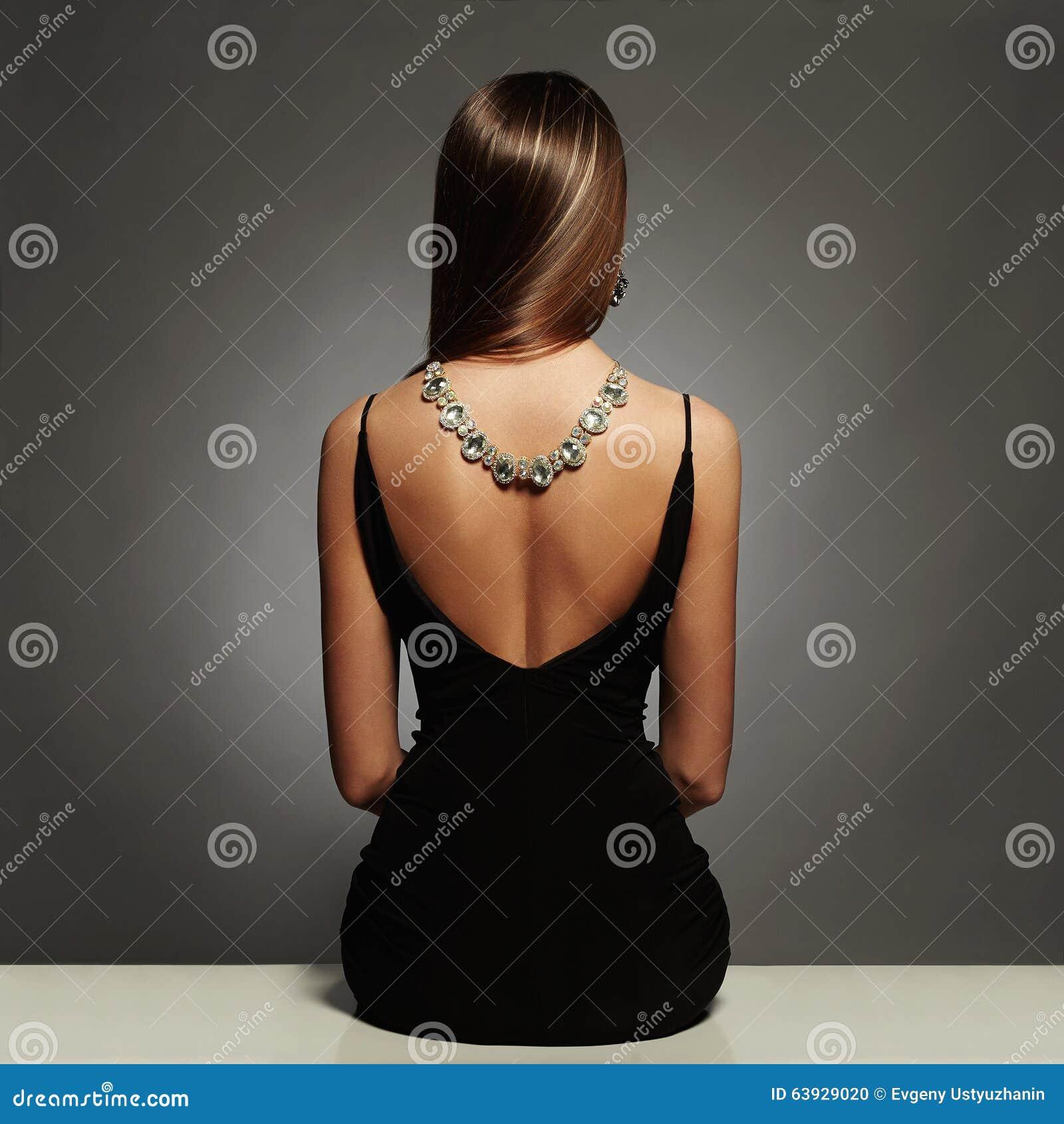Piękny plecy młoda kobieta w czarnej seksownej sukni luz piękno brunetki dziewczyny siedząca dziewczyna z kolią na ona z powrotem