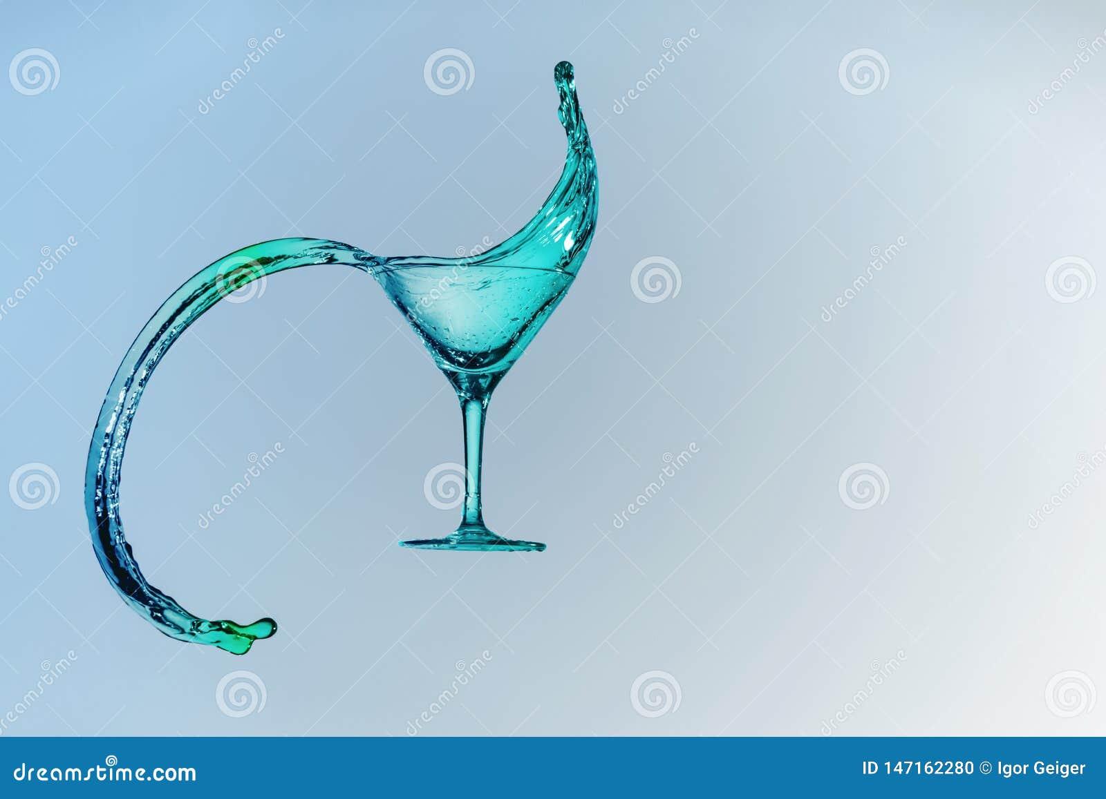 Piękny pluśnięcie ciecz od Martini szkła na błękitnym gradientowym tle