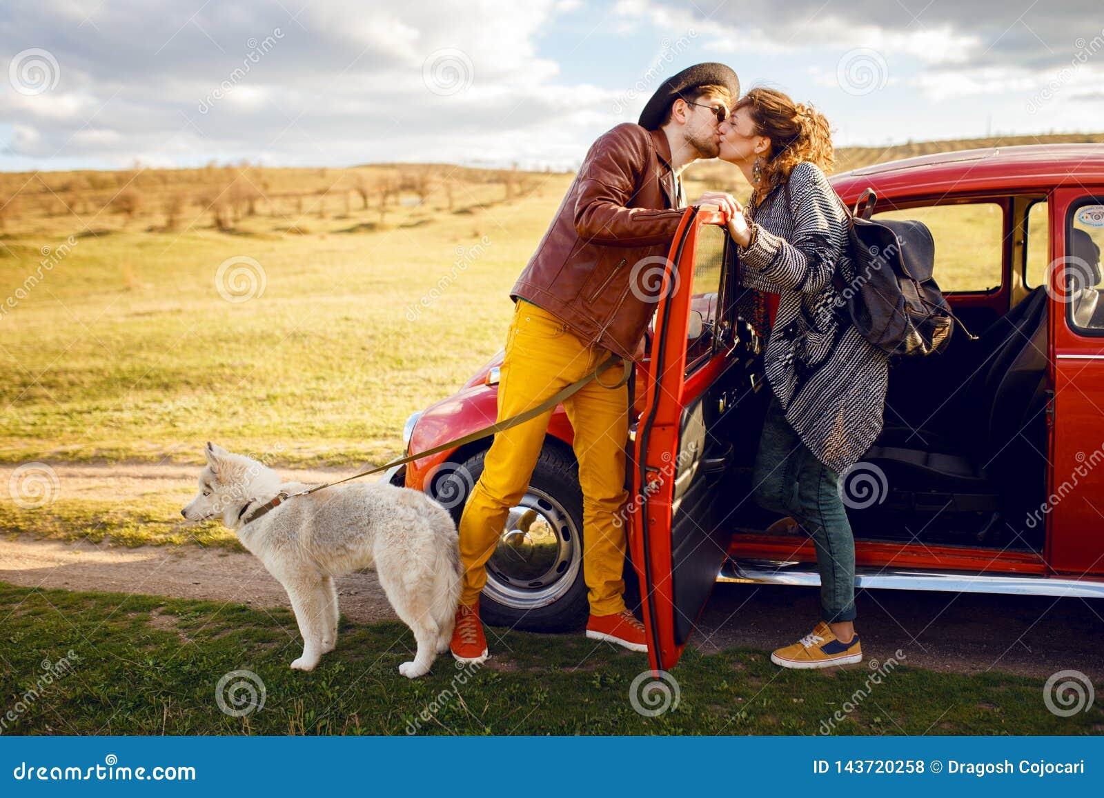 Piękny portret potomstwa dobiera się, blisko rocznika czerwonego samochodu z ich husky psem, odizolowywającym na natury tle