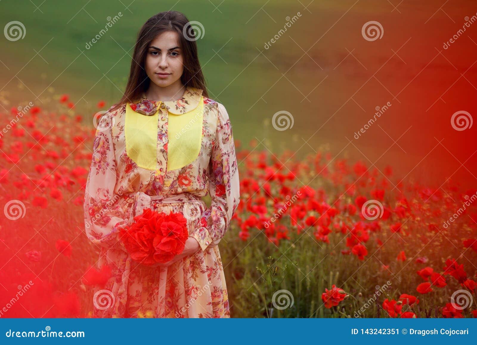 Piękny portret potomstwa tęsk brąz z włosami kobieta, ubierająca w kwiecistej sukni, stoi w czerwonym maczka polu