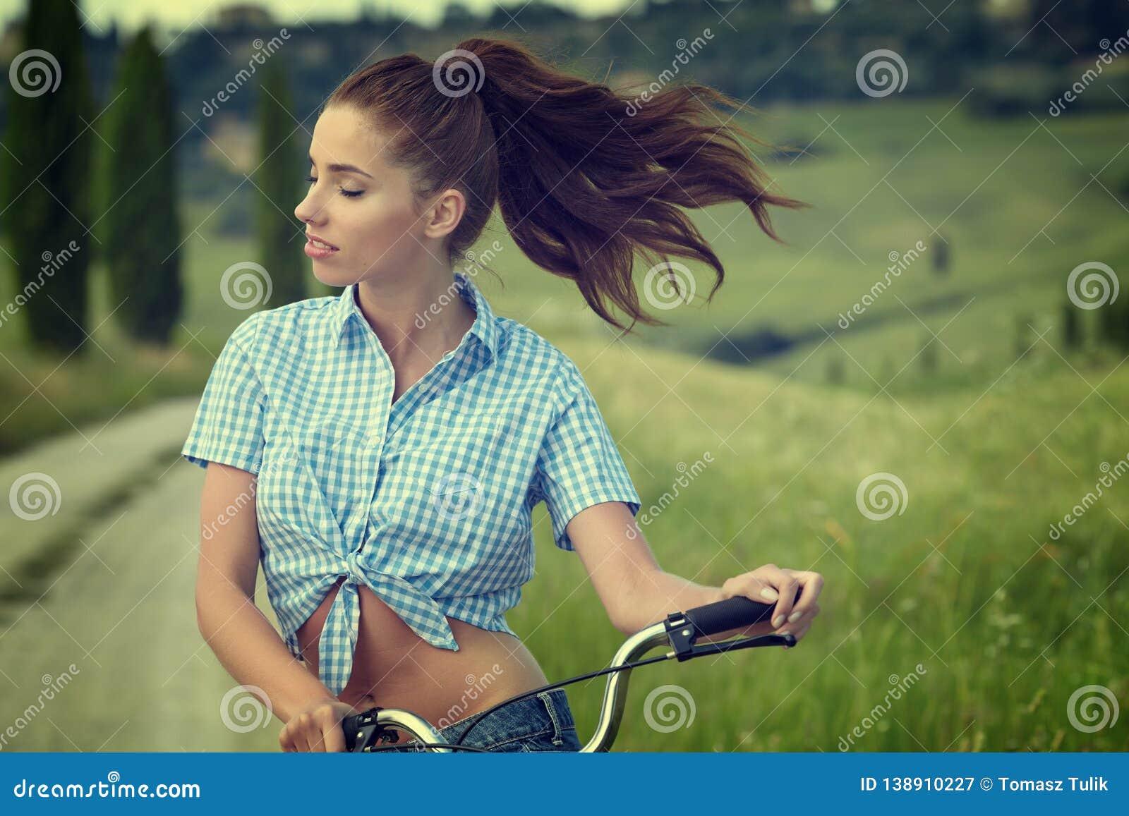 Piękny rocznik dziewczyny obsiadanie obok roweru, lato czas