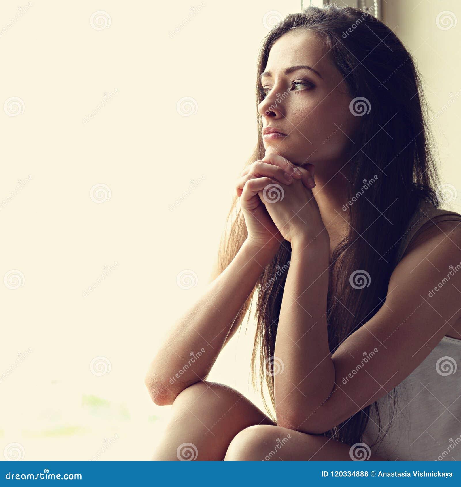 Piękny smutny osamotniony kobiety obsiadanie, lookin i główkowanie wokoło i