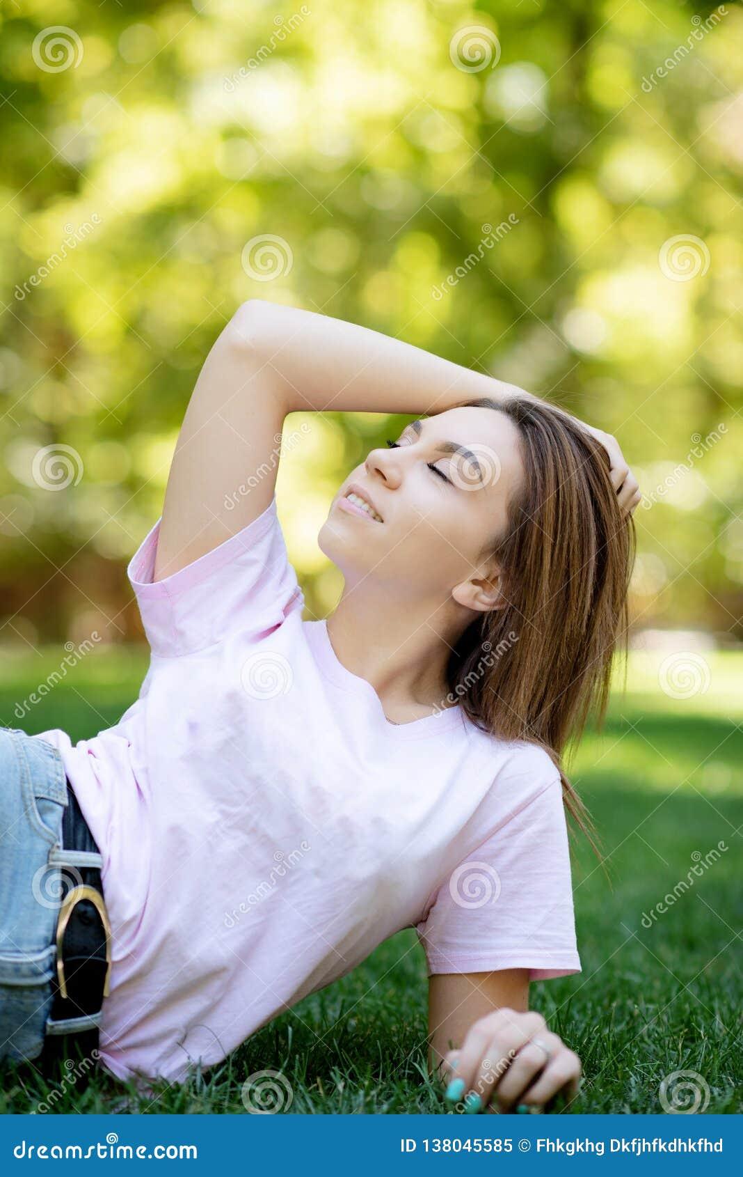 Piękny uśmiechnięty kobiety lying on the beach na trawie plenerowej Jest całkowicie szczęśliwa styl życia, wakacje