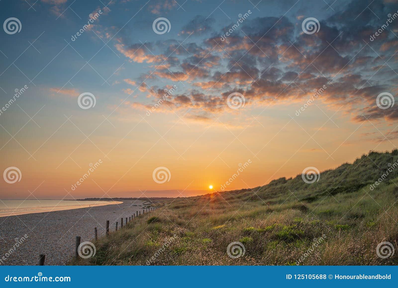Piękny wibrujący lato zmierzchu plaży krajobraz z stunning sk