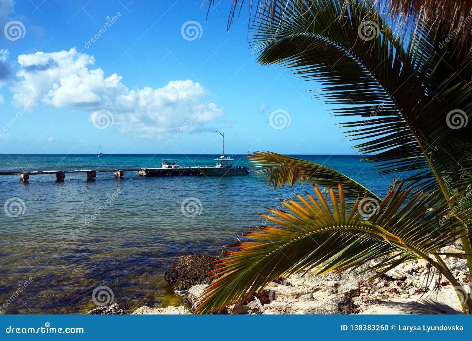 Piękny widok morze karaibskie błękitny morze, łamany most i łódź od piaskowatej plaży z błękitów krzesłami na wyspie,